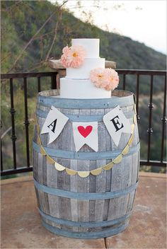 White cake with floral accents on wine barrel with cute bunting! Captured By: Alyssa Marie Photography ---> http://www.weddingchicks.com/2014/05/09/lucky-penny-wedding-tradition-you-will-love/