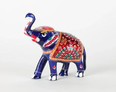 A colorful elephant figurine made in the traditional art form of Meenakari in India. Meenakari is the art of coloring and ornamenting the surface of metals by fusing over it brilliant colors that are decorated in an intricate design. Colorful Elephant, Elephant Figurines, Marigold, Traditional Art, Art Forms, Animals Beautiful, Elephants, India, Gifts