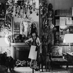 A Look at 24 Fireplaces in _Vogue_. Cecil Beaton captures Coco Chanel in front of the fireplace in her Paris apartment—the mantel's simple lines are almost eclipsed by the ornate belongings that surround it. Photographed by Cecil Beaton, Vogue, February,