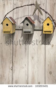 Grouping similar birdhouses by mounting them on a single board and adding decoration gives them a greater presence.