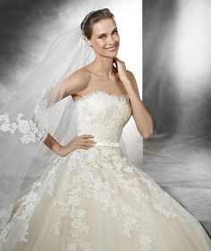 TREY- Tulle princess dress in tulle with lace appliqués with a sweetheart neckline. Beige underlay. Bodice with sweetheart neckline edged with a scallop. Full tulle skirt decorated with lace appliqués. Mikado silk belt with a small bow at the waist.