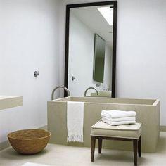Salle de bains avec baignoire et sol en pierre blanche du Wisconsin et miroir très haut avec cadre en bois foncé