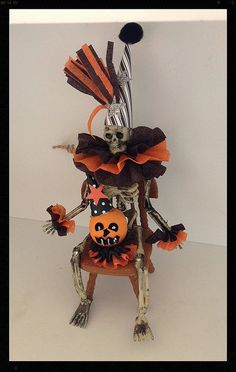Halloween decoration  A six inch skeleton is wearing a crazy party hat and a fluffy crepe paper collar and matching cuffs He is sittingin a dollhouse chair and has a handmade jack o lantern sitting in his lap   Can sit or hang  comes with a twine loop for hanging.  Halloween ornament