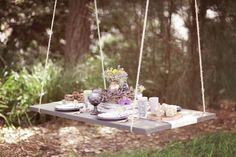 table suspendue décoré d'un centre floral, un chemin de table blanc et des sucreries