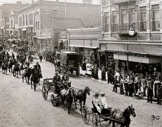 A street scene in the 19th Century - more prosperous towns had wooden sidewalks along the dirt roads
