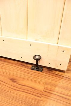 A floor guide from Home Depot keeps the bottom of the door in place. The rubber circular section at the top gently keeps the door from banging around.