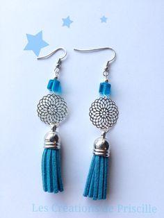 Boucles d'oreilles percées, pompons en suédine bleu, estampes en forme de rosaces argentées et petites perles cubes bleues.  longueur des BO: 7cm environ  Ces BO peuvent être adaptées en clip sur demande lors de la commande
