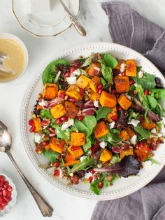 Roasted Butternut Squash Salad made with pomegranates, pistachios, goat cheese, and a cumin-spiced date dressing. Perfect for Thanksgiving or Friendsgiving!
