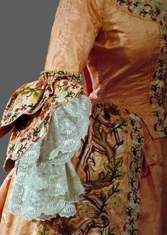 Detail sleeve, robe à la francaise, probably Spain, c. 1720. Salmon coloured ribbed silk, lavishly embroidered with floral motifs.