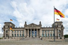 Parliament building of Germany / Reichstag Building - Reichstag Building in Berlin with waving german flags and summer sky.