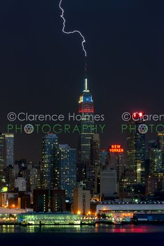 Lightning strikes the antenna on the top of the Empire State Building in New York City during a summer thunderstorm on Thursday, July 26, 2012.  The Empire State Building, which is struck by lightning an average of just under 100 times annually, was illuminated in colors of various nations in celebration of the 2012 London Olympics.  Prints available at http://clarence-holmes.artistwebsites.com/featured/empire-state-building-lightning-strike-i-clarence-holmes.html