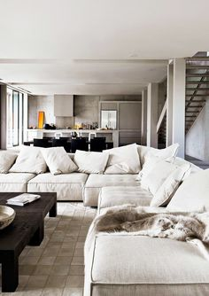 Minimalist living room with a large gray sectional, and a wood coffee table