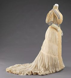 Silk and linen evening dress (side view), by Lord & Taylor, American, 1900-02. Lord & Taylor, like many New York City department stores in the late-19th and early-20th century, had on-site workrooms where they could produce custom garments. This evening dress, with its notable contrast of refined cutwork lace on the bodice and net lace of the skirt, is a good example of the type of work produced by the store.