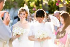 The brides are absolutely glowing as they make their way down the aisle | Luna Gardens Events