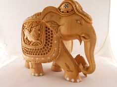 Hand carved elephant inlaid with ebony and camel bone.  The elephant with its trunk down indicates a peaceful elephant.