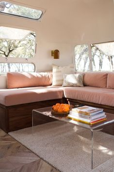 Storage under the blush-toned sofa makes it easy to keep the area neat. A CB2 coffee table sits above a Dash & Albert rug, and the sconces have been sourced from Schoolhouse Electric. Kaindl flooring and Benjamin Moore's Dune White shade have been used throughout the space. #camper #mobilehome #airstream #smallspace