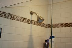 SUBWAY TILE WITH GLASS ACCENT TRIM AND HASGROHE SHOWER HEAD