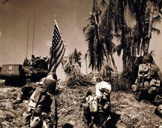26-G-3634_Box 70_1: Invasion of Leyte, Philippines, 20 October 1944. First American Flag of Liberation Raised on Leyte at H-Hour Plus Two Minutes. From a Coast Guard-Manned LST, the sixth wave in the swift succession of amphibious thrusts against the beach of Leyte island advances with guns ready. The American Flag, first to be planted by Liberation Forces on that sector of the invasion beach, was placed in the shell-torn palm tree at H-Hour plus two minutes. U.S. Coast Guard photograph...