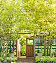 A stripped-down fence and airy plants offer subtle screening. Two oversize urns planted with rhododendrons mark the transition from public face to private space.  The open latticework fence offers a discrete but unmistakable barrier; bright green paint and wood framing gives it distinctive character. Double doors are a steadfast signal of a secluded area; the latticework details and wood inserts neatly complement the contrasting fence pieces.