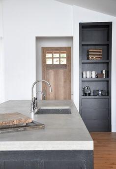 dark grey cabinets, marble and wood island, wood wall (fridge)