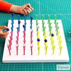 """Make your own board game with a 12""""x 12"""" foam-core board that's at least 1/2-inch thick (available at art-supply stores), golf tees, and marbles in two colors."""