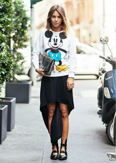 A Mickey Mouse sweatshirt is paired with a high-low skirt, Acne boots, and a metallic clutch