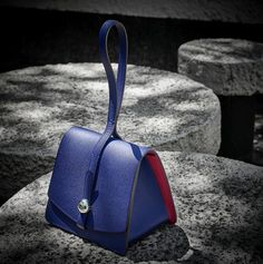 Moynat The architectural lines of the Madeleine clutch play on the contrast of clean, spare lines and the rounded palladium closure. The sharp contrast of colours lends the Madeleine a young, joyous touch. #Moynat #MadeleineClutch Photo: @jerome_bryon