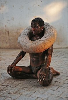 "Pakistani wrestler or ""Pahalwan"" with a neck weight made of solid stone"