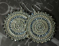 Bold and bright extra large disk earrings created with various shades of silver lined and metallic11.0 and 8.0 seed beads. The outer edges are adorned with bright metallic silver Swarovski crystals. Over 500 individually sewn beads are woven to make these beautiful earrings. The French