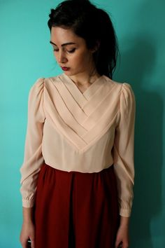 Beautiful blouse with a dark red skirt.