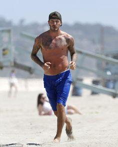 David Beckham runs to talk to a photographer on the beach of Malibu, California