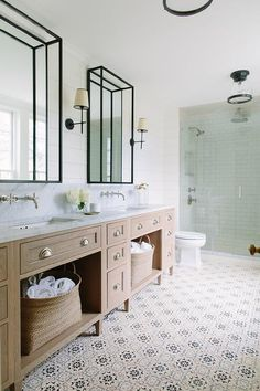This well appointed bathroom is lit by Thomas O'Brien Bryant Sconces mounted to a white shiplap flanking bronze framed mirrors.