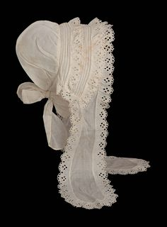 Woman's cap with deep brim with two rows of pin tucks and three layers of ruffles with eyelets; two long lapet-like ties down front with same eyelet ruffle; casing with large ties at nape ofneck