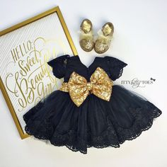 This beautiful black and gold party dress has so many lovely details! The black satin bodice features black lace short sleeves. The puffy, layered soft tulle sk
