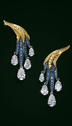 Earrings in platinum and 18k gold with pearshaped white diamonds, sapphires and yellow diamonds.