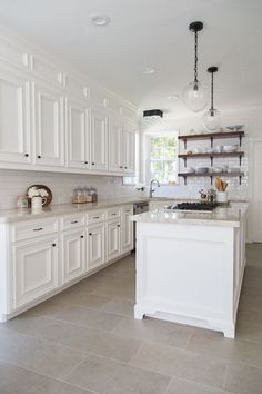 Beautiful Farmhouse kitchen remodel - used to be dark with oak cabinets, added a box and paneled it above the cabinets to give an illusion of taller cabinets, tiled wall, open shelving, Taj Mahal quartzite countertops, seeded glass pendant lights