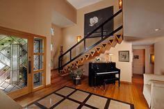 rambarde escalier design en bois colorée en noir, parquet massif et marbre au sol