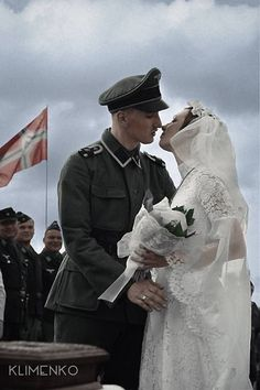 "Accompanied by his fellow comrades, a soldier adorning his full uniform of the elite 1st SS Panzer Division ""Leibstandarte 'Adolf Hitler'"" kisses his bride during a wedding ceremony thoughtfully held by the members of his unit."
