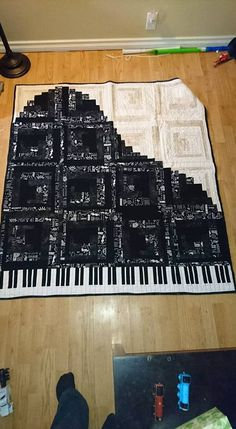 """From: Desi Stanley """"Music for my soul."""" I don't have a pattern. It is just a log cabin block. Half the block is 1 inch strips and the other is 2 inch creating a curve instead of the straight diagonal. the blocks i used ended up being 14 inch I think. so this is a throw quilt. The keys I just worked out the math 5o make them fit after I had the piano done."""