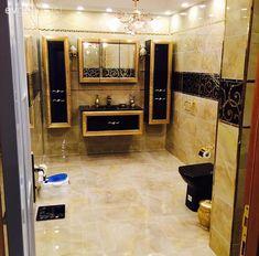 Siyah ve altın detaylarla lüks bir görünüm kazanan banyo.