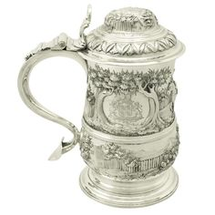 By English Silversmiths Thomas Whipham  & Charles Wright  made  1765 An exceptional, large and impressive antique Georgian English sterling silver baluster shaped quart tankard This exceptional George III sterling silver quart tankard has a plain baluster form onto a spreading circular foot. The body of this antique tankard is encircled with an applied girdle and embellished with exceptional later chased  Style  note the influence  of French Huguenot emigre Paul de Lamerier