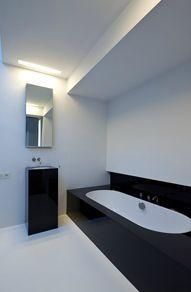 badkamer: De hele ruimte is wit en het bad en de lavabo krijgen een zwart contrast.