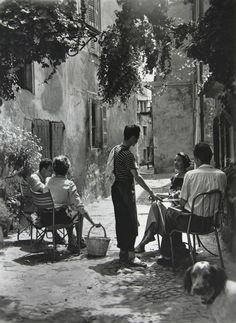 In a French village (1950s) Love every detail in this photo. The light, her basket, the cobblestones, the dog.