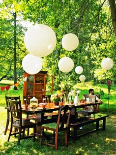 LOVE the floating lights and the formal dinner table outdoors under a big shade tree!