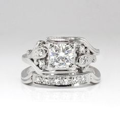 Dont miss out on this early 1940s wedding set with curved bands and a unique design! Finding wedding sets with the original engagement ring AND wedding band are a rare find these days! Especially in this condition! The engagement ring is set with a central transitional cut diamond weighing approximately .53cts and is graded G color, VS clarity. There are four .03ct bead set single cut diamonds surrounding that glittering diamond and they have comparable quality. The engagement ring has a…