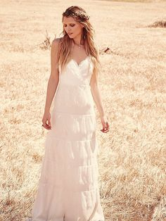 Tiered Lace Maxi   This dress is delicate and feminine.  The wrapped bodice is made up of lace and a subtle floral appliqué.  The silk body is covered in tiered eyelash lace.  Hidden zip in back with a hook and eye closure.  Low back.  Lined.     *By Erin Fetherston