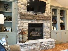 You can't go wrong with over-grouted stone, a antique hand hewn beam mantle, and custom built-in cabinets in a sage green tone. Fireplace With Cabinets, Craftsman Fireplace, Fireplace Bookshelves, Fireplace Built Ins, Home Fireplace, Fireplace Remodel, Built In Cabinets, Living Room With Fireplace, Built In Shelves Living Room