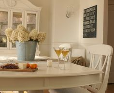 Shabby chic dining room with white painted hutch, buffet, table, chairs/galvanized vase with dried hydrangea/modern typography panel artwork/martini glasses/Hello Lovely Studio