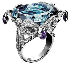 Piaget blue topaz ring. Limelight ring embroidery motif in 18K white gold, set with one brilliant-cut blue topaz (approx. 45 ct), pear-cut purple sapphires and brilliant-cut diamonds.