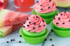 Three easy Watermelon Cupcakes with pink buttercream frosting and chocolate chips next to two slices of freshly cut watermelon.